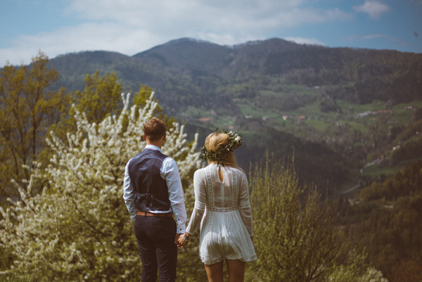 Bride and groom looking at Slovenian countryside