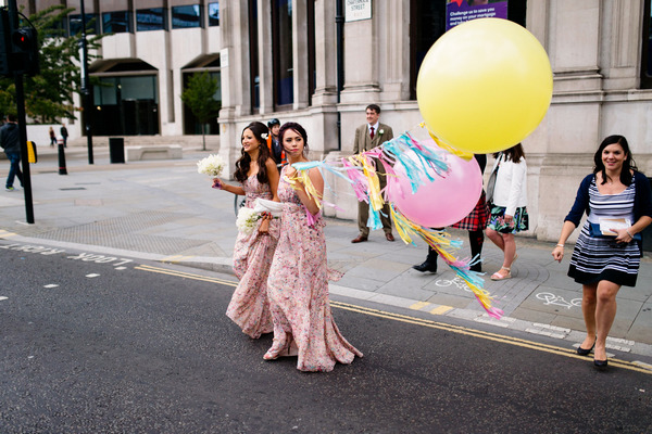 Bridesmaids crossing the road with balloons