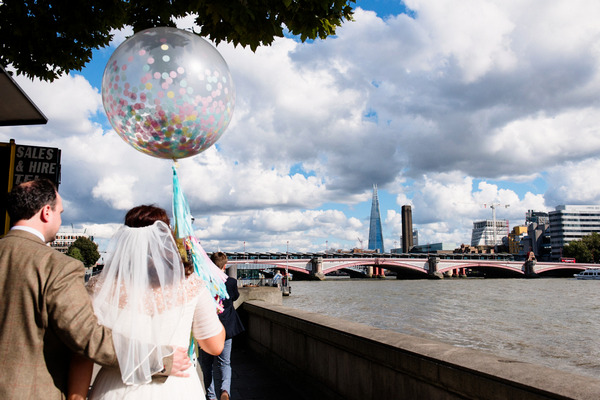 Bride and groom walking along River Thames in London