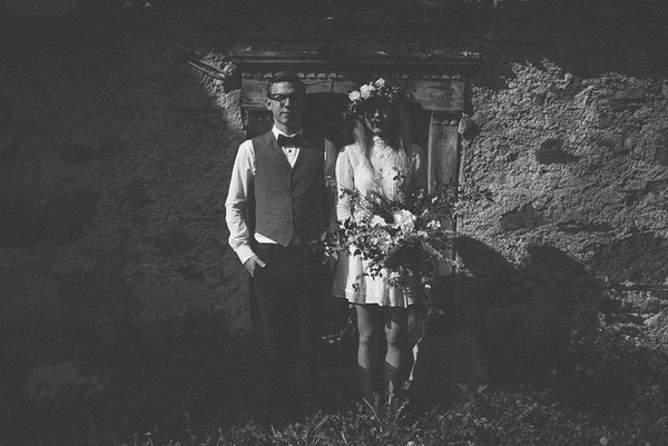 Bride and groom standing outside house