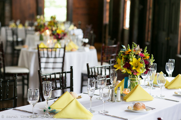 Yellow napkins and bright flowers on wedding table