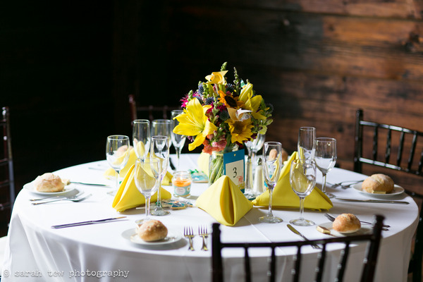 Round wedding table with bright flowers and yellow napkins