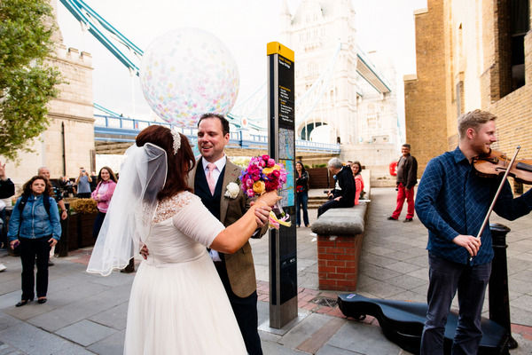 Bride and groom dancing to busker in London