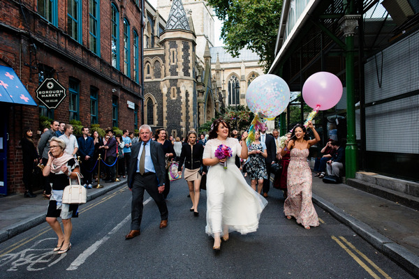Wedding party walking through London to wedding reception at Roast