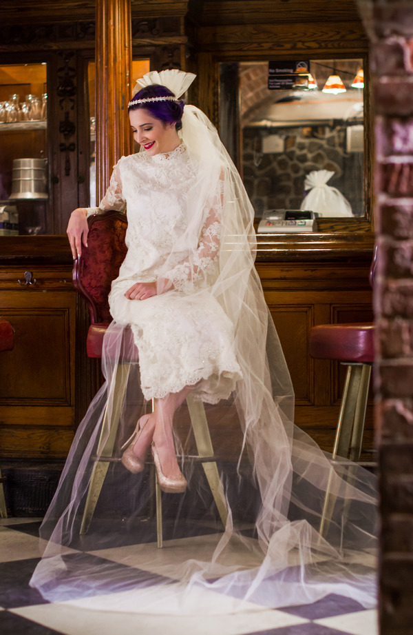 Bride wearing vintage wedding dress and long veil, sitting on bar stool