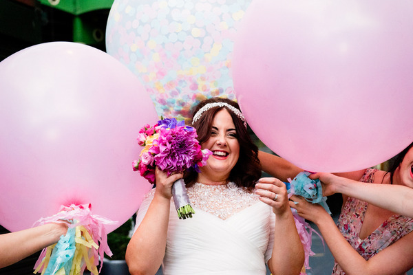 Bride surrounded by large pink balloons