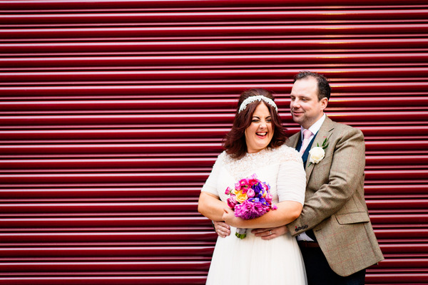 Bride and groom by red shutter