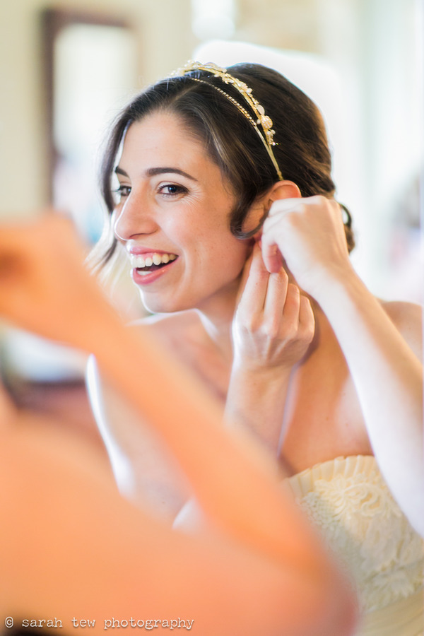 Bride putting on earring while looking in mirror