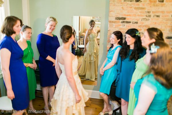 Bride looking in mirror with bridesmaids