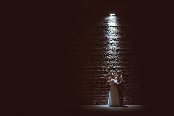 Bride and groom by wall under spotlight