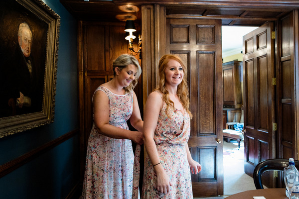 Bridesmaids helping each other with dresses
