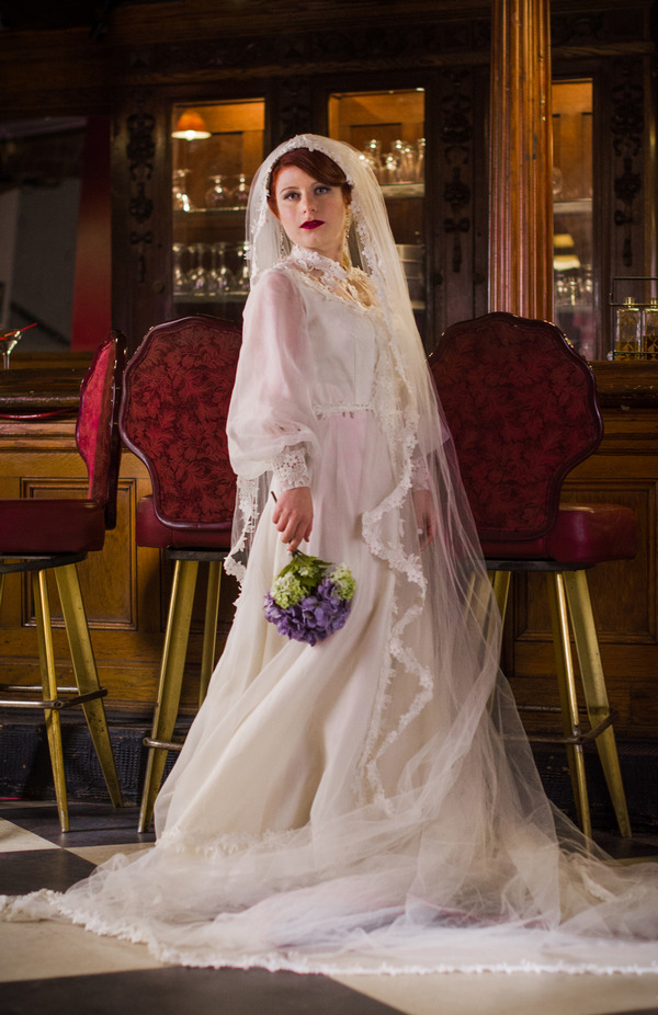 Bride wearing vintage wedding dress and long veil
