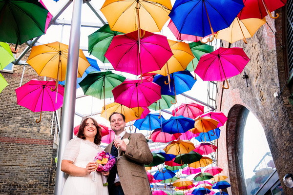 Bride and groom under colourful umbrellas in Borough Market