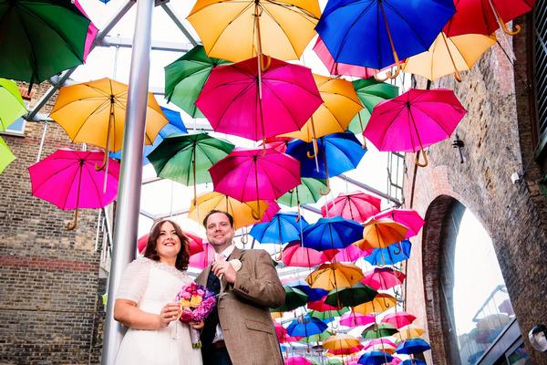 Bride and groom under colourful umbrellas in Borough Market
