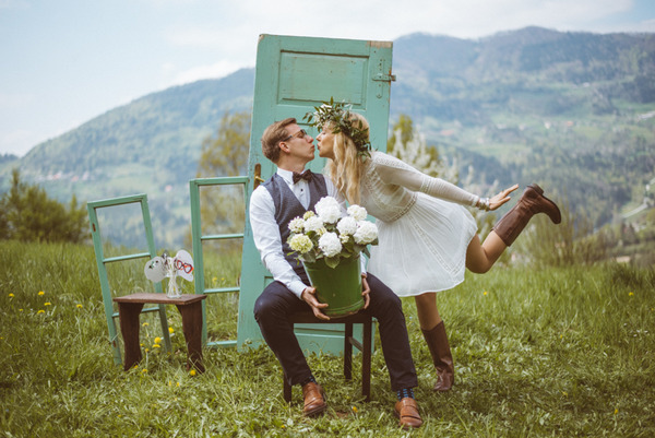 Couple about to kiss in front of rustic door in Slovenian countryside