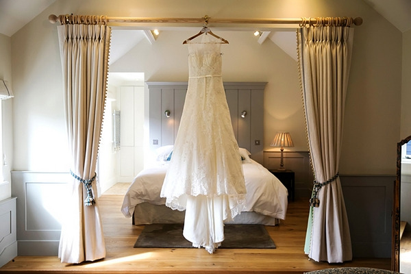 Wedding dress hanging in front of bed