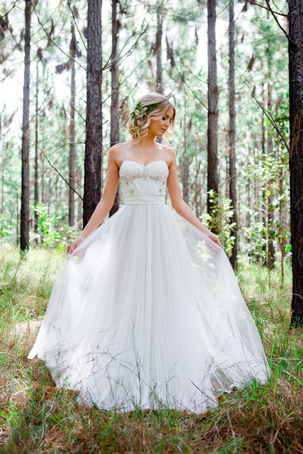 Bride standing in woodland holding out dress