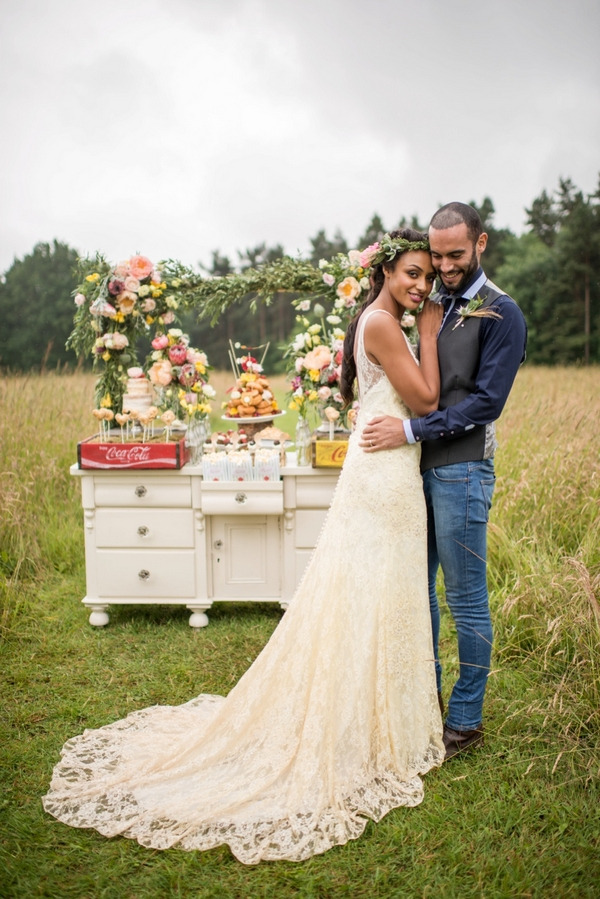 Bride and groom standing in meadow in front of rustic dresser of wedding cakes and desserts