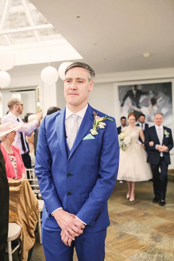 Groom in blue suit with bride walking down aisle behind him
