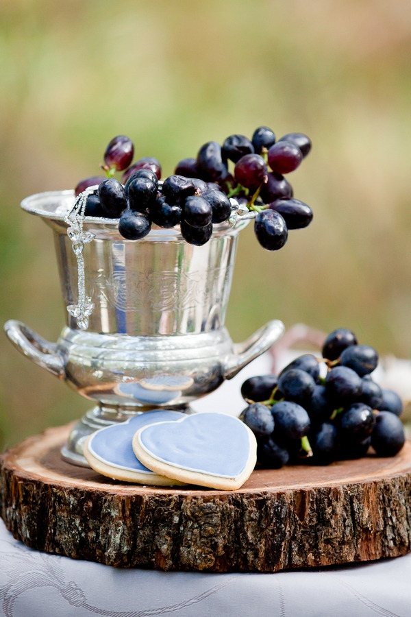 Silver bucket of grapes on log slice