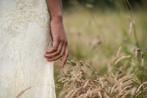 Bride's hand by corn in meadow