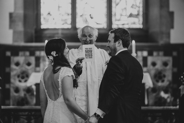 Vicar holding up You May Now Kiss The Bride sign - Picture by Blavou Wedding Photography