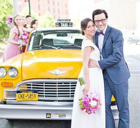 Bride and groom posing in front of yellow Ney York taxi - Picture by Cassi Claire