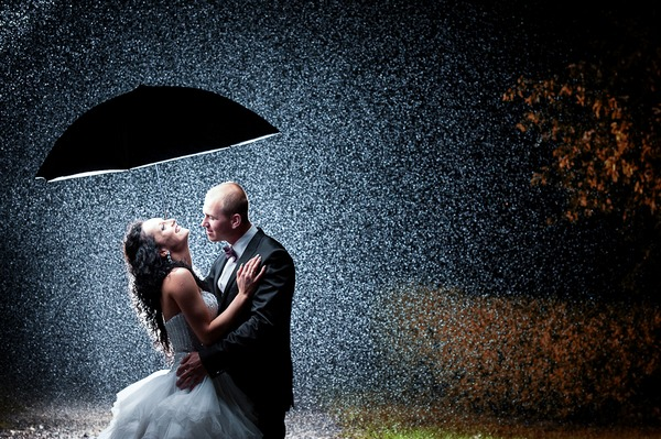 Bride and groom standing under umbrella in pouring rain - Picture by Umbrella Studio