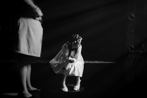 Young flower girl sitting waiting for the bride - Picture by Benjamin Stuart Photography