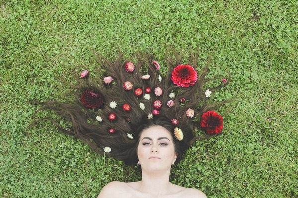Bride lying on grass with flowers on her long dark hair