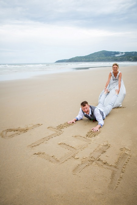Bride pulling groom across the beach with help written in the sand - Picture by Lindy Yewen Photography