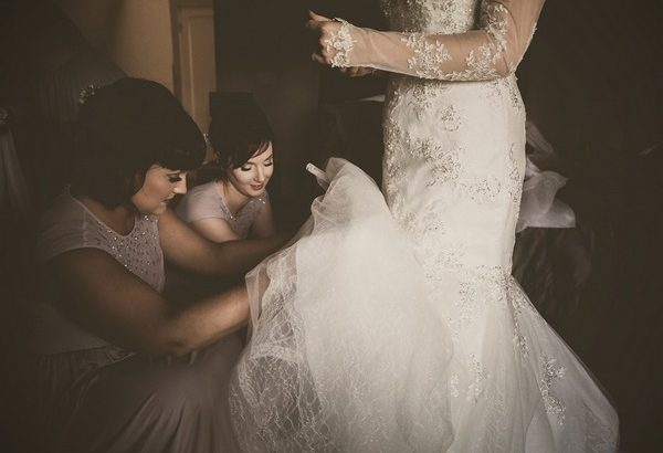 Bridesmaids helping bride with wedding dress - Picture by Tracey Warbey Photography