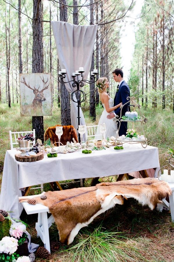 Bride and groom standing behind wedding table in woodland