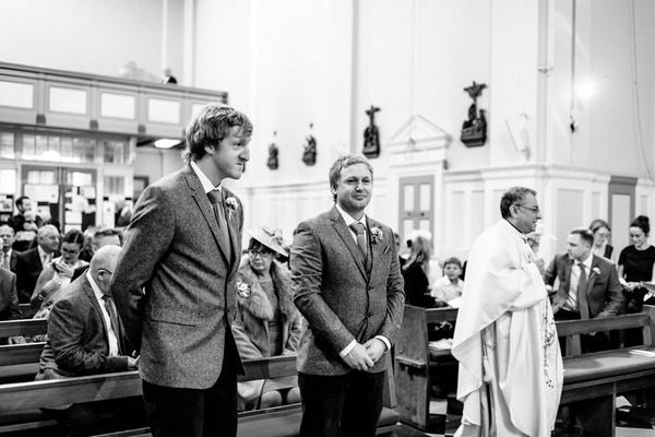 Groom and best man waiting for bride at altar