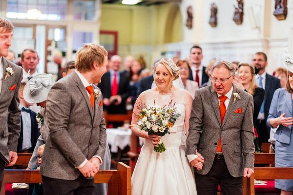 Groom turning to see bride walk down aisle