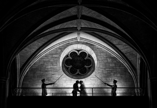 Bride and groom kissing on balcony as two soldiers hold up swords - Picture by Paul Keppel Photography