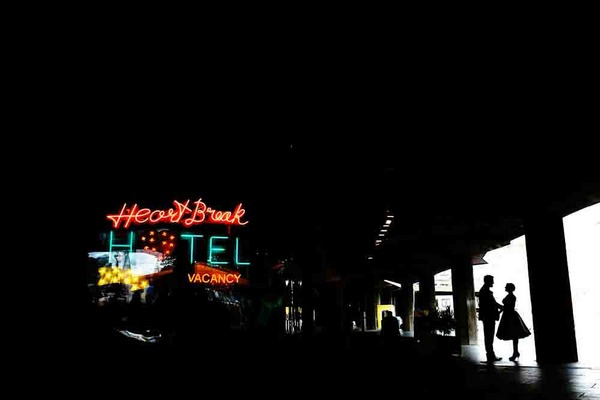 Bride and groom standing near illuminated Heart Break Hotel sign - Picture by Lyndsey Goddard Photography