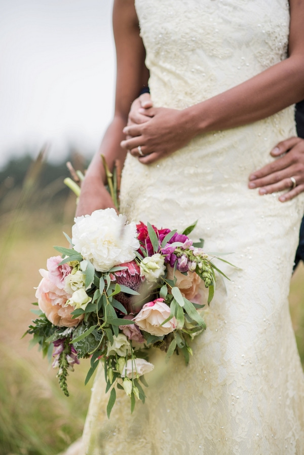 Bride's rustic wedding bouquet and groom's arm around her waist
