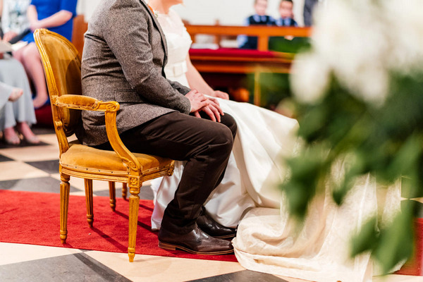 Bride and groom sitting holding hands in church