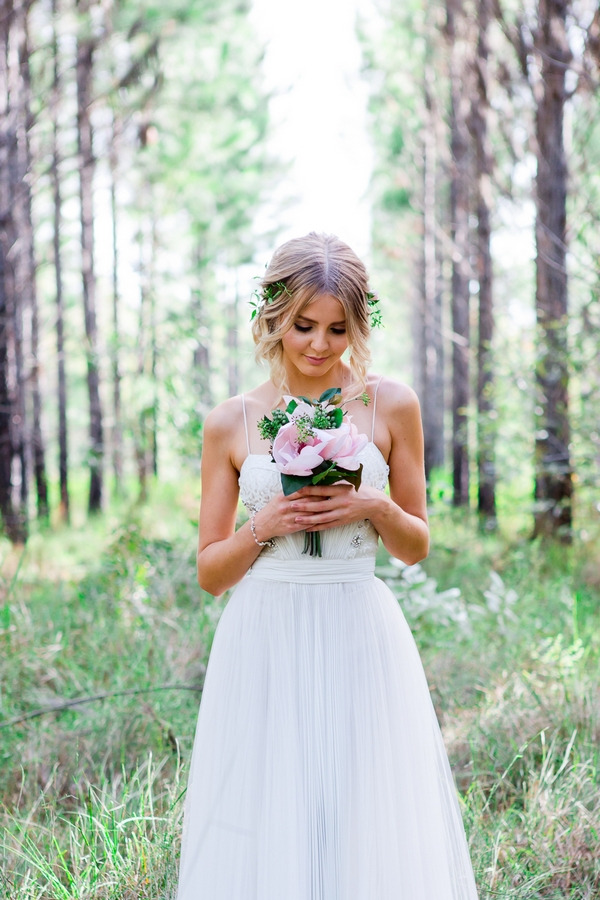 Bride looking down at bouquet in woodland