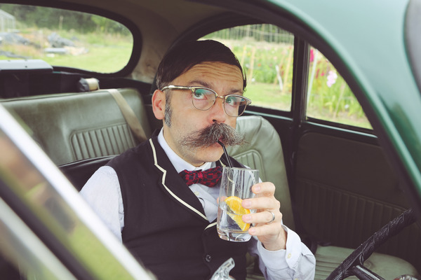 Man sitting in Morris Minor drinking gin and tonic
