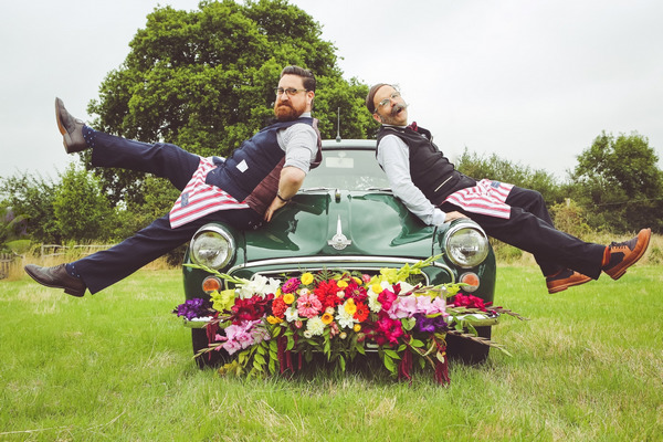 Men leaning on bonnet of Morris Minor with flowers on bumper