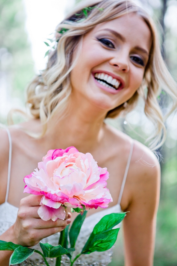 Bride holding large flower and smiling