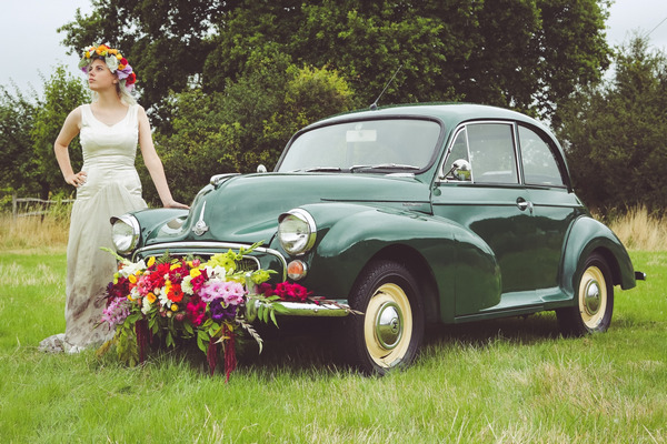 Bride standing next to green Morris Minor