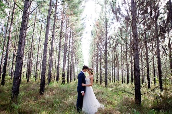 Bride and groom facing each other in woodland
