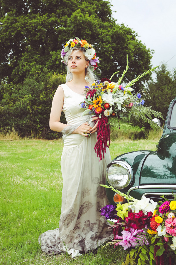 Bride wearing flower crown holding bouquet next to Morris Minor