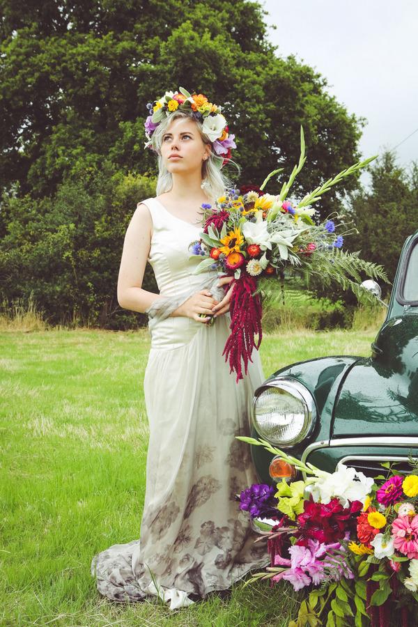 Bride wearing flower crown holding bouquet next to Morris Minor
