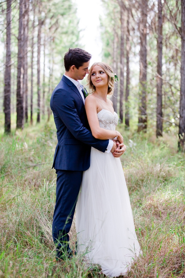 Groom standing behind bride with arms around her waist