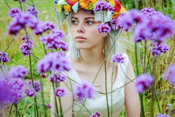 Bride sitting in field of purple flowers
