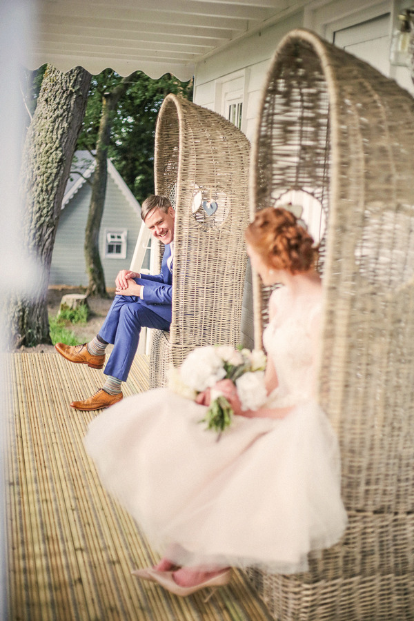 Bride and groom sitting on chairs looking at each other outside house at Woodhill Hall